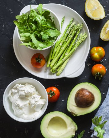 Photo for Healthy food ingredients - avocado, asparagus, tomatoes, sheep cheese, arugula on dark background, top view. Healthy clean eating concept - Royalty Free Image