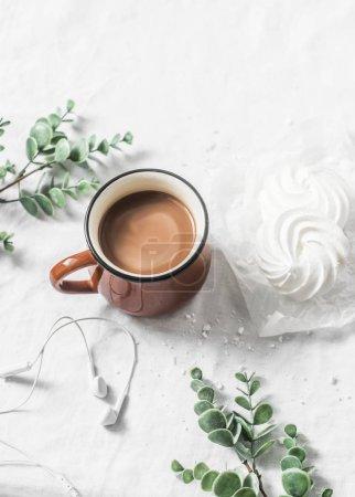 Photo pour Poser à plat la tasse de cacao et la meringue sur un fond blanc. Petit déjeuner matin inspiration avec musique casque - image libre de droit