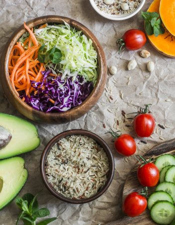 Photo for Healthy vegetarian food set background. Cabbage salad, avocado, tomatoes, cucumbers, pumpkin, wild rice on a paper background, top view. Flat lay - Royalty Free Image