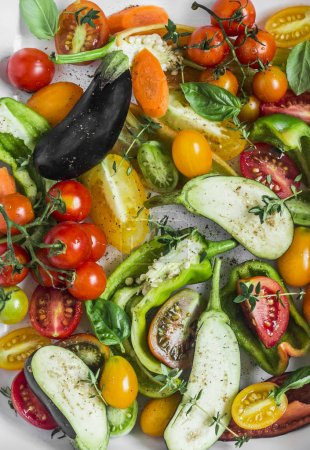 Photo for Mix raw seasonal vegetables cooking. Eggplant, bell pepper, tomatoes, carrots, zucchini, cherry tomatoes, spices, olive oil close up. Weight loss, diet vegetarian food concept. Flat lay - Royalty Free Image