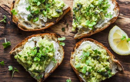 Photo for Avocado, cream cheese toast with micro greens on a rustic wooden board, top view. Good fats healthy eating concept. Delicious breakfast or snack - Royalty Free Image