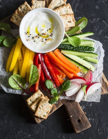 Photo for Weight loss concept of a healthy diet food. Mix vegetables and greek yogurt sauce on a wooden rustic cutting board. Sweet pepper, carrot, cucumber, radish and yogurt sauce. Flat lay - Royalty Free Image