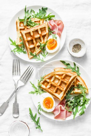 Photo for Served breakfast with potatoes savory waffles, boiled egg, ham and arugula on light background, top view. Appetizers, snack, brunch. Delicious healthy food concept. Flat lay - Royalty Free Image