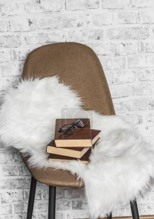 Photo for Brown soft loft style chair, fur rug, stack of books on light wall background. Interior concept, copy space - Royalty Free Image