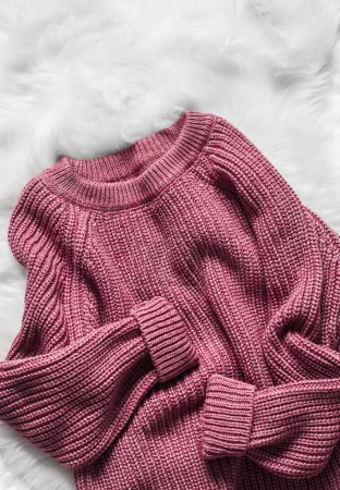Photo pour Pull femme en laine framboise couleur sur un tapis moelleux blanc, vue de dessus. Concept de mode - image libre de droit