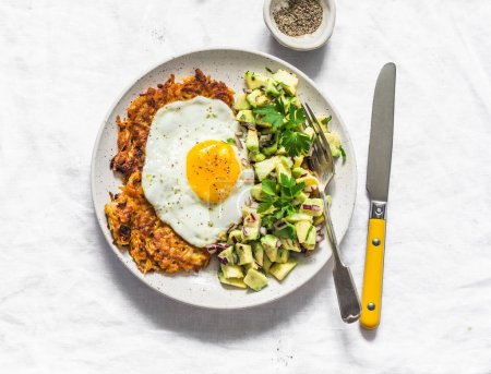 Photo for Sweet potato rostis with fried egg and avocado salsa on light background, top view - Royalty Free Image