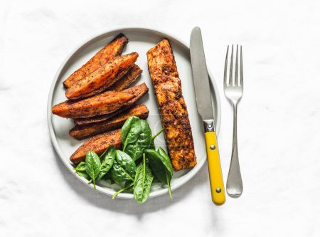 Photo for Crispy spice crust baked salmon with sweet potato and spinach - healthy balanced lunch on light background, top view - Royalty Free Image