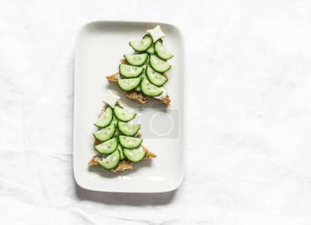 Photo for Creative children's sandwiches in the form of a Christmas tree with cream cheese and cucumber on a light background, top view - Royalty Free Image