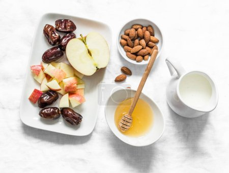 Photo for Ingredients for honey almonds apples protein smoothies on a light background, top view. Dates, almond milk, dates, honey, almonds - ingredients for a healthy diet drink - Royalty Free Image