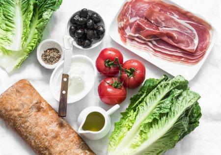 Photo pour Ingrédients pour bruschetta - prosciutto, pain ciabatta, salade romano, olives, tomates, fromage à la crème sur fond léger, vue de dessus. Plate-forme - image libre de droit