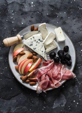 Photo pour Plaque d'entrée - prosciutto, gorgonzola, brie fromage, olives, pommes, noix amandes sur fond foncé, vue du haut - image libre de droit