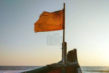 Foto de La bandera golpeada en el arco del barco fluye sobre el fondo del mar y el sol de puesta. Ventanas de sol e iluminación a color. - Imagen libre de derechos