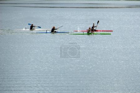 girls rowing on kayaks on the lake.