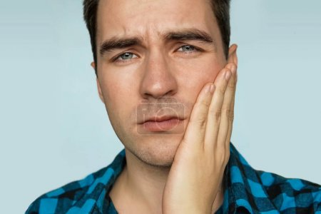 Photo pour Un jeune garçon avec une émotion triste sur son visage en tenant sa main sur la mâchoire du patient sur un fond bleu. Portrait d'un homme dans une expression douloureuse avec un mal de dents. - image libre de droit
