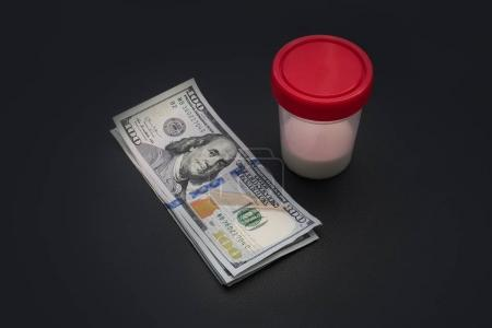 Photo pour L'homme a donné son sperme pour analyse. l'argent gagné sur le sperme. médecine reproductive. l'achat de spermatozoïdes. argent et récipient en plastique sur fond noir. bon argent facile - image libre de droit