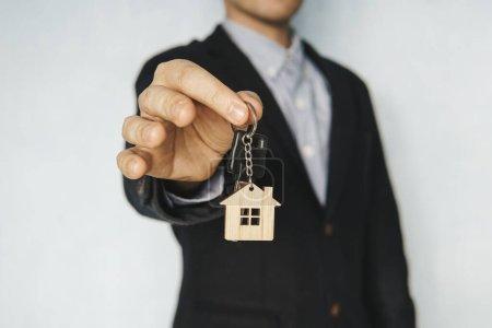 Photo pour Tenir les clés de la maison sur un porte-clés en forme de maison. concept de vente de biens immobiliers. Location d'un appartement. Louer une chambre. - image libre de droit