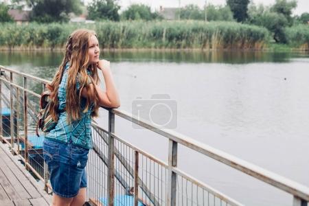 Teenager girl walks across the bridge before rain