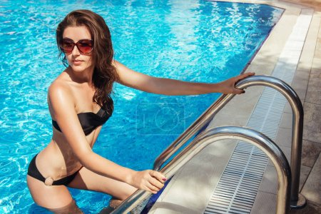 Sexy woman goes out of the swimming pool