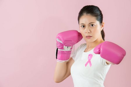 Sporty Asian girl wear boxing gloves anti-cancer