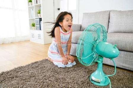 happy little girl playing electric fan at home