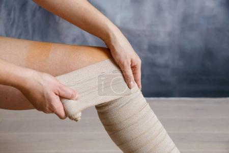 Photo pour Patiente atteinte de varices appliquant un bandage de compression élastique après la chirurgie. Traitement curatif, prévention de la thrombose et concept des soins de santé aux personnes âgées . - image libre de droit