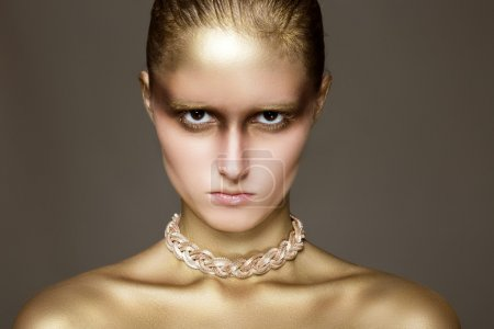 Young woman with stylish gold make-up