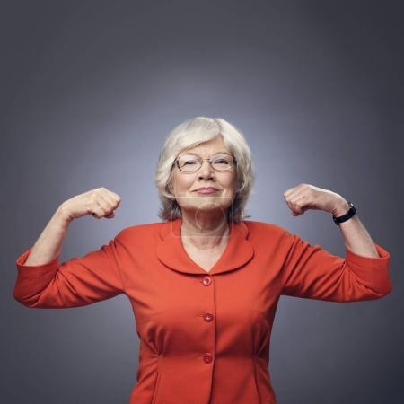 Photo pour Dame âgée souriante montrant ses muscles sur fond gris avec espace de copie - image libre de droit