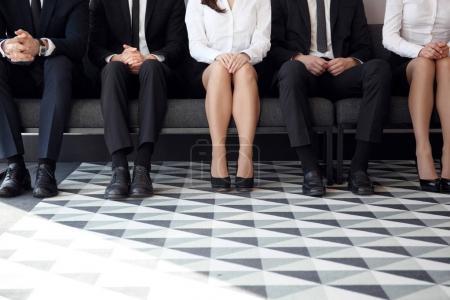 Photo pour Personnes en attente d'un entretien d'embauche assis sur des chaises dans une rangée - image libre de droit