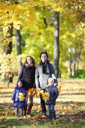 Photo for Happy family with two children walking in autumn park holding hands - Royalty Free Image