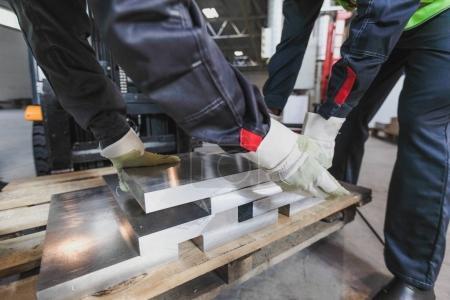 Photo pour Travailleurs prenant des billettes en aluminium à l'atelier CNC - image libre de droit