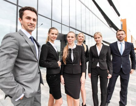 Photo for Portrait of successful business people team standing together outdoors near modern office building - Royalty Free Image