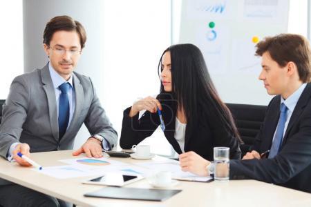 Photo pour Travailleurs à la réunion de présentation des rapports financiers au bureau moderne en regardant d'affaires - image libre de droit