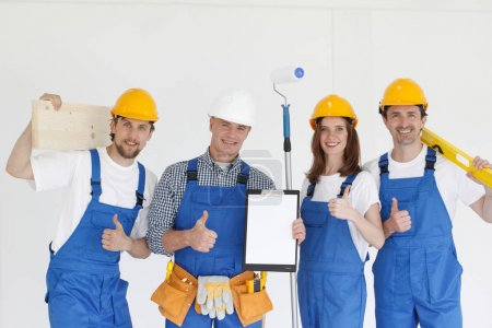 Photo for Team of happy smiling workers with tools and contract - Royalty Free Image
