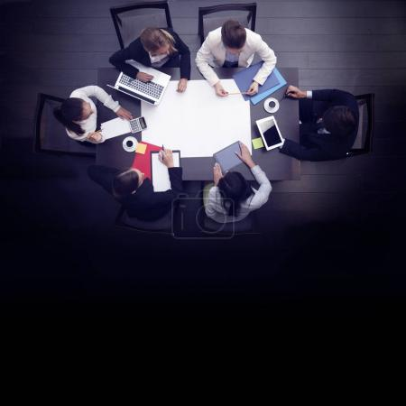 Photo for Business workplace with people, cup of coffee, digital tablet, smartphone, papers and various office objects on table - Royalty Free Image