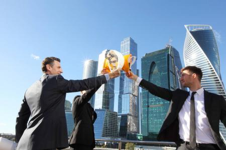 Foto de Grupo de empresarios que tintinea sus cascos como un éxito en el fondo de rascacielos, construcción acabado concepto - Imagen libre de derechos