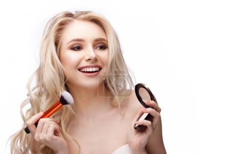 happy girl doing her makeup