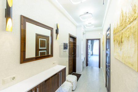 A long corridor in the apartment with beige Wallpa...