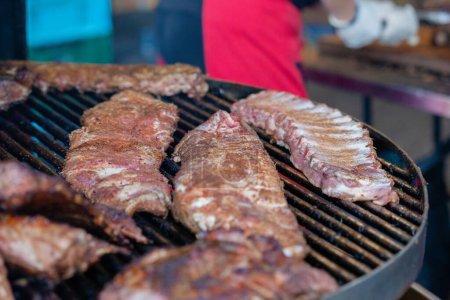 Photo pour Côtelettes de porc grillées sur le gril au festival des aliments de la rue - image libre de droit