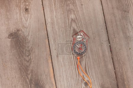 Plastic compass over a wooden background