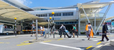 AUCKLAND, NEW ZEALAND - NOVEMBER 23, 2017 People including Indian woman in orange sari crossing road towards entrance to international airport terminal.