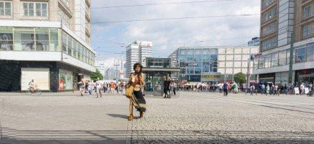 Photo pour Berlin, ALLEMAGNE - 28 AOÛT 2017 ; Scène de rue de la ville avec des gens errant et la gare et les marchés à distance et fille de style hipster regardant mobile et tenant de la crème glacée comme elle traverse la rue . - image libre de droit