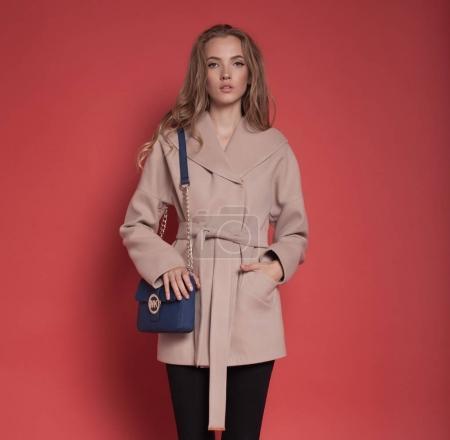 Photo pour Belle jeune femme en manteau posant sur fond rouge - image libre de droit