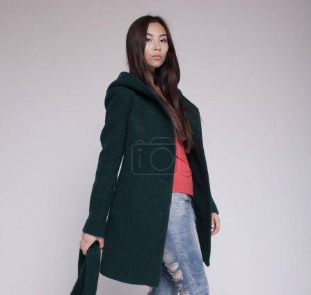 Foto de Modelo asiático de moda en ropa de otoño/invierno posando en fondo claro - Imagen libre de derechos