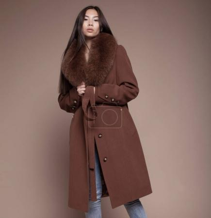 Photo for Fashionable glamorous asian girl with long hair wearing classy winter coat and posing at studio and looking at you or in camera. Fashion vogue style indoor portrait - Royalty Free Image
