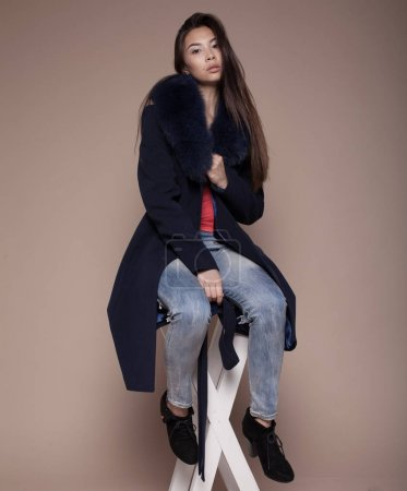 Photo pour Fashionable glamorous asian girl with long hair wearing classy winter coat and posing at studio and looking at you or in camera. Fashion vogue style indoor portrait - image libre de droit