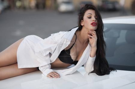 Photo for Fashion outdoor photo of beautiful glamour woman with long brunette hair posing beside a luxury car - Royalty Free Image