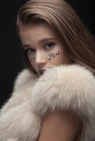 Photo pour Beauté mode modèle fille en manteau de fourrure de vison bleu. Belle femme d'hiver de luxe avec une écriture créative faire va te faire foutre sur le visage - image libre de droit