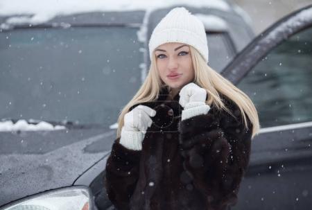 Photo pour Portrait d'hiver extérieur d'une femme blonde souriante près d'une voiture noire. Neige autour . - image libre de droit