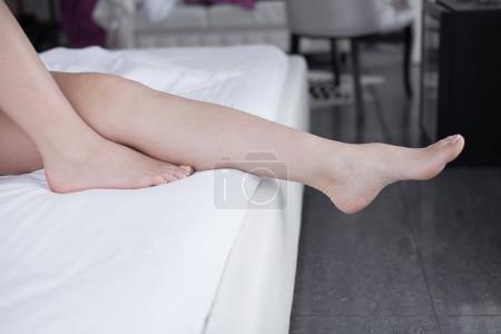Photo pour Jambes nues d'une jeune femme dort dans son lit à la maison. mettre l'accent sur les jambes. - image libre de droit