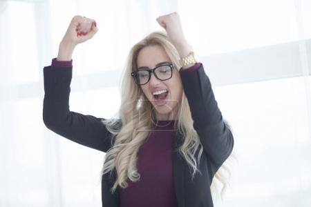 Foto de Mujer de negocios exitosa celebrando con los brazos en alto . - Imagen libre de derechos